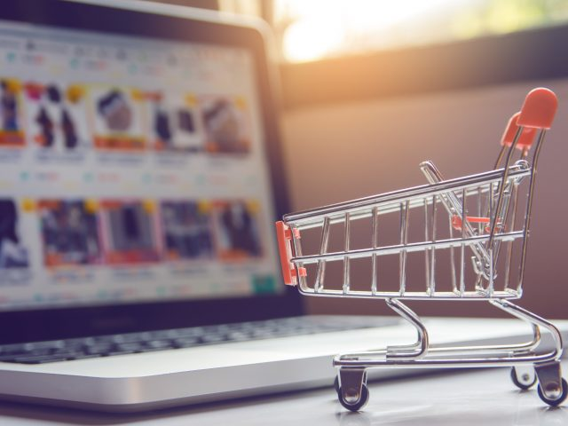 Shopping online concept - Empty shopping cart or trolley and laptop on white table. Shopping service on The online web. with copy space